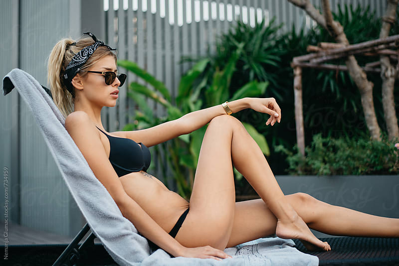 Attractive Blonde Woman Sunbathing in Black Bikini by Nemanja Glumac for Stocksy United