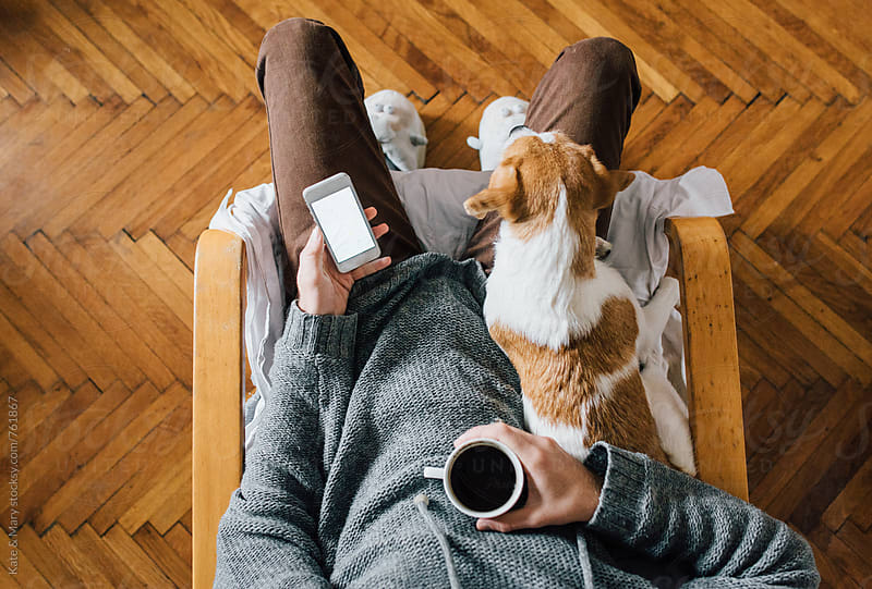Man sitting with a dog and holding a cup of coffee and mobile phone by Katarina Simovic for Stocksy United