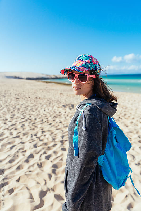 Hipster young woman wearing a big sweatshirt, pink sunglasses and a colourful cap in a beach, with copyspace by Inuk Studio for Stocksy United