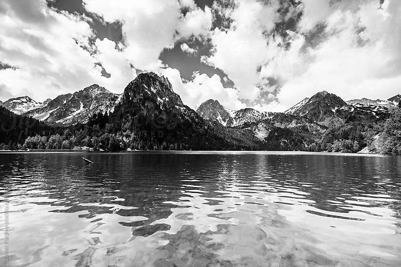 snowy peaks of mountains reflected in the lake  by Javier Pardina for Stocksy United