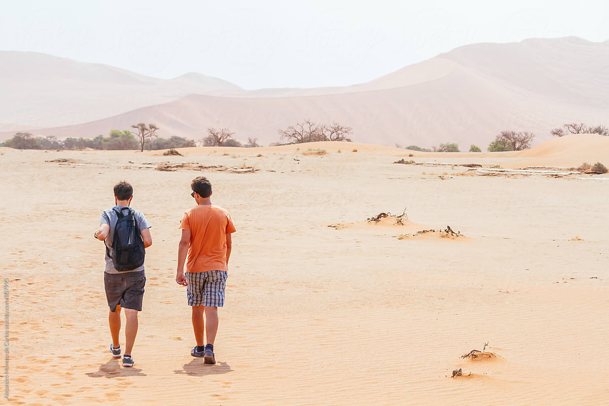 back view of two young friends walking in the desert in the middle