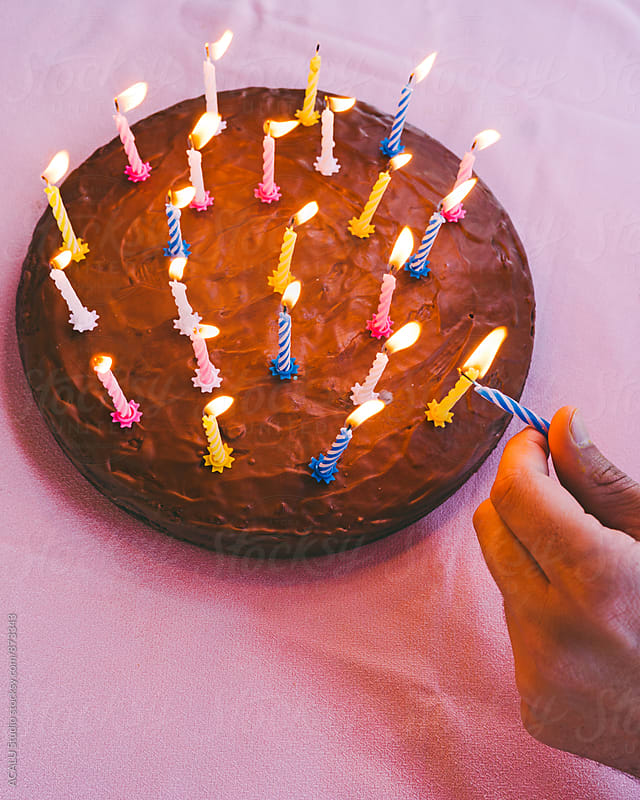 Hand lighting candles on a cake by ACALU Studio for Stocksy United