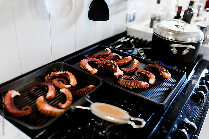 Cooking a lot of fresh octopus tentacles on slabe on kitchen stove by Laura Stolfi for Stocksy United