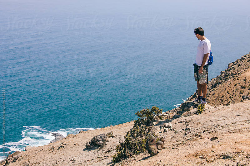 Young adventurer man on top of a cliff on the desert looking down to the ocean by Alejandro Moreno de Carlos for Stocksy United
