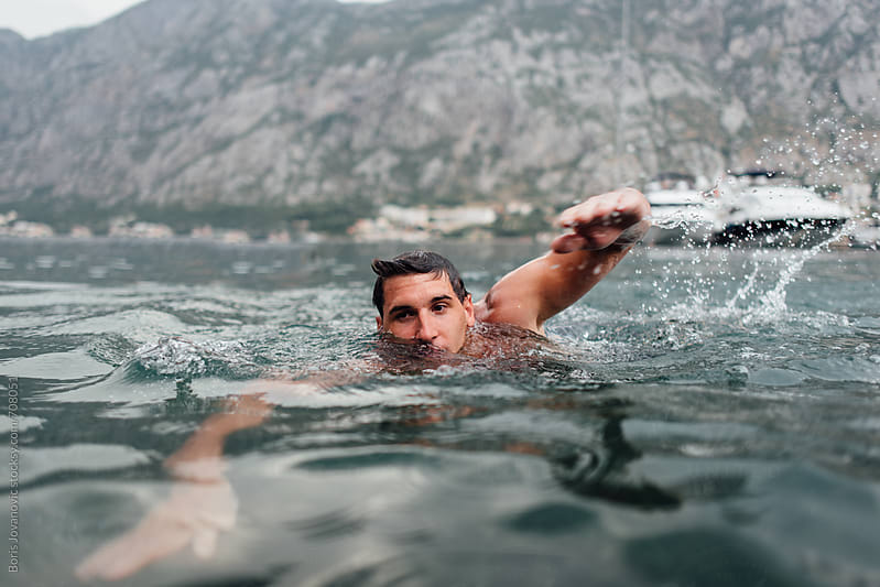Man swimming in the sea by Boris Jovanovic for Stocksy United