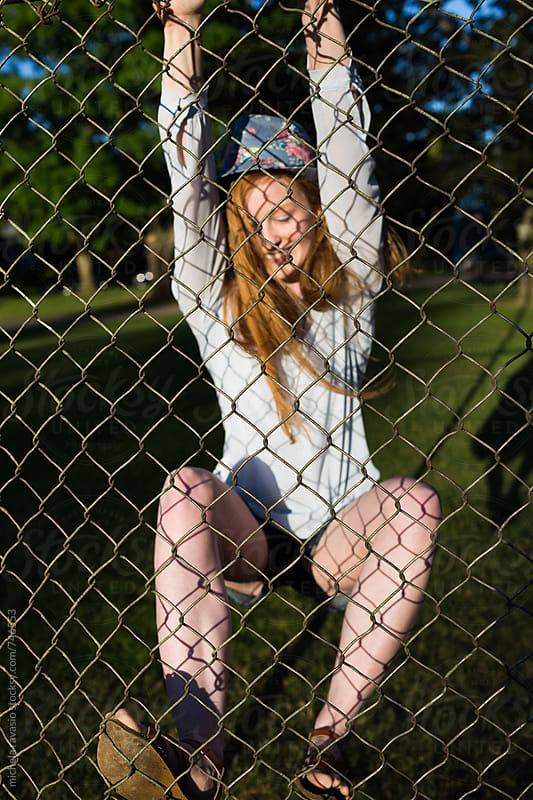 Girl climbing over a fence by michela ravasio for Stocksy United