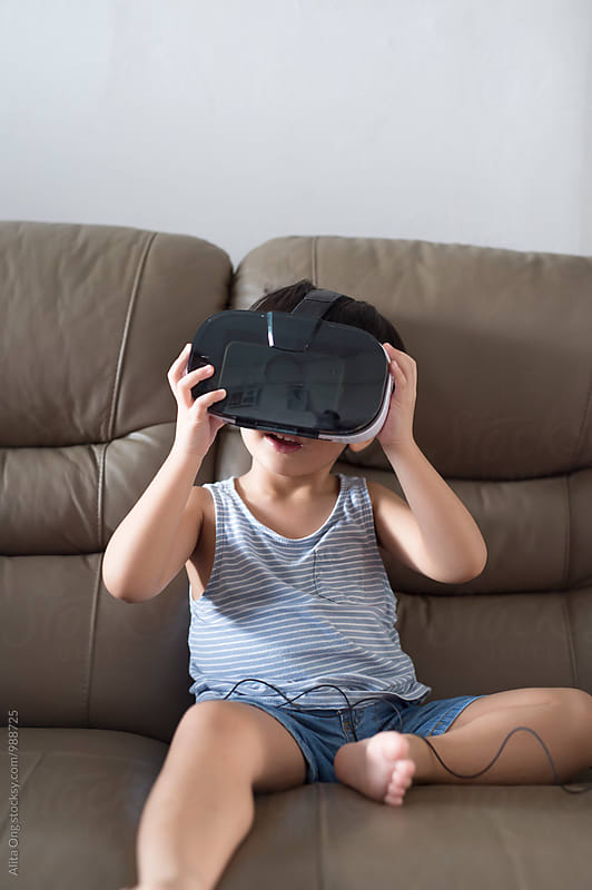 Little boy wearing VR headset by Alita Ong for Stocksy United