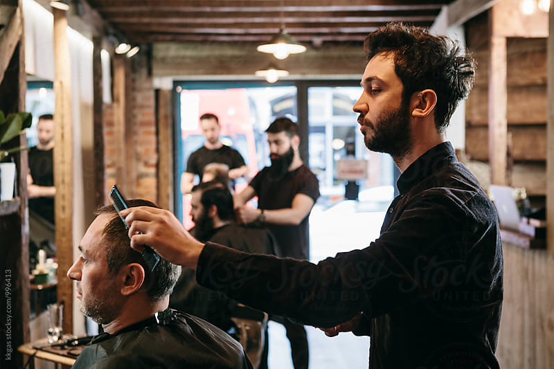 A busy barbershop with barbers and customers by kkgas for Stocksy United