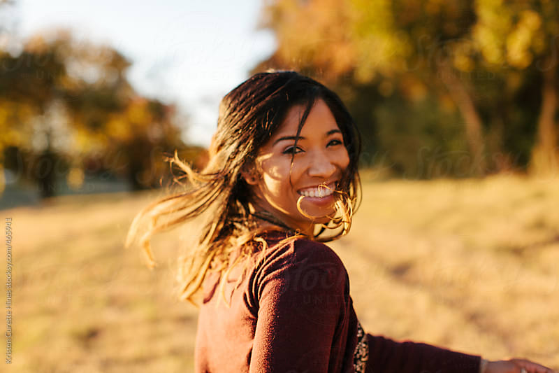 Young woman's portrait with sunlight effect in nature.  by Kristen Curette Hines for Stocksy United