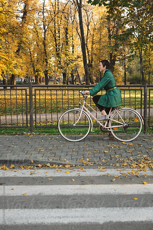 Pretty Woman in a Green Trench Coat Riding Her Bike by Katarina Radovic for Stocksy United