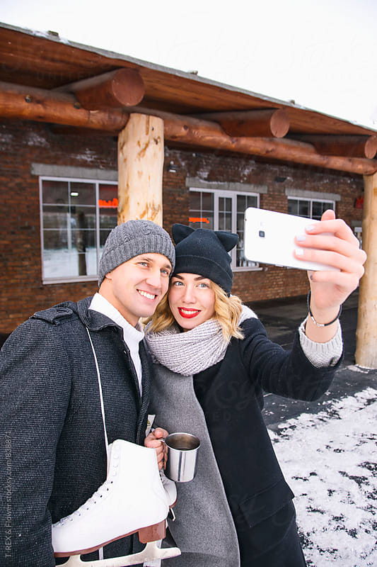 Portrait of young couple taking selfie by Danil Nevsky for Stocksy United
