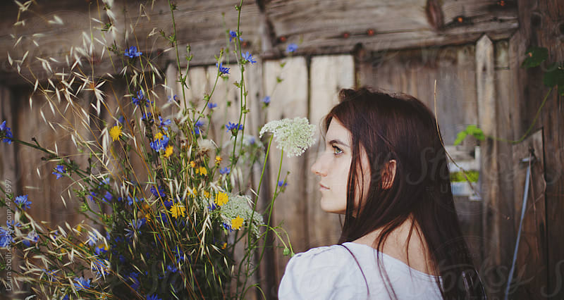 Celebrating spring: profile of woman seen from behind with mixed flowers by Laura Stolfi for Stocksy United