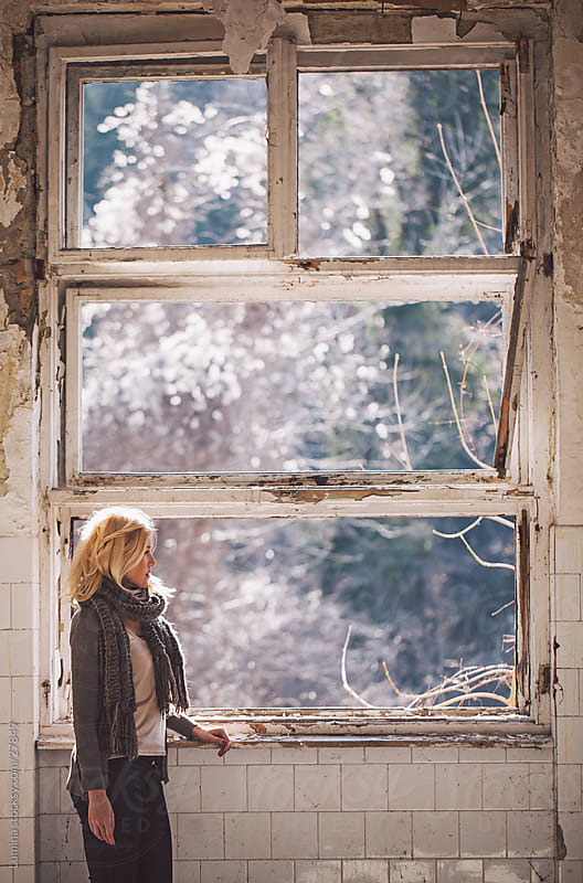 Sad Woman Standing by an Old Window by Lumina for Stocksy United