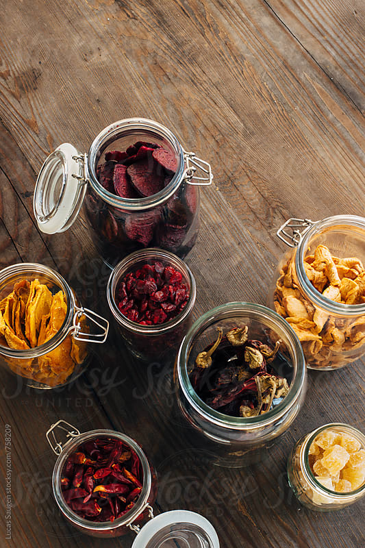 Glass jars of dried fruits and peppers from above. by Lucas Saugen for Stocksy United