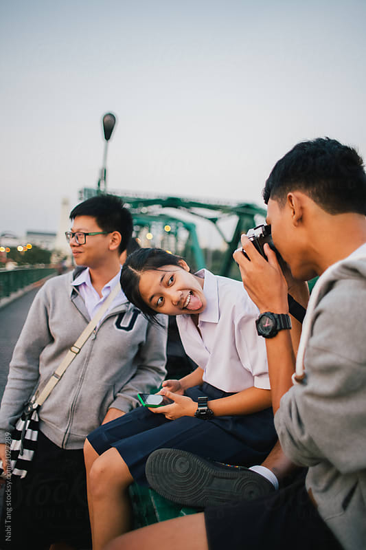 Thai teenagers in high school student uniform sitting casually on the bridge at sunset time by Nabi Tang for Stocksy United
