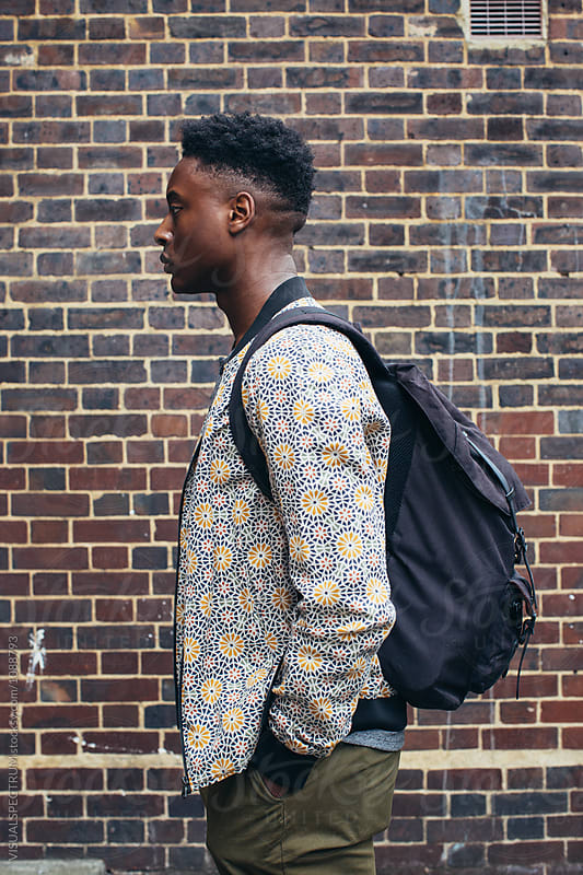 Profile of Young Fashionable Black Man Standing in Front of Exposed Brick Wall by VISUALSPECTRUM for Stocksy United