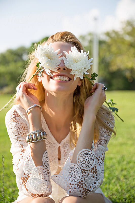 Beautiful blonde woman dressed in white lace covering her eyes with white flowers and smiling  by Jovo Jovanovic for Stocksy United