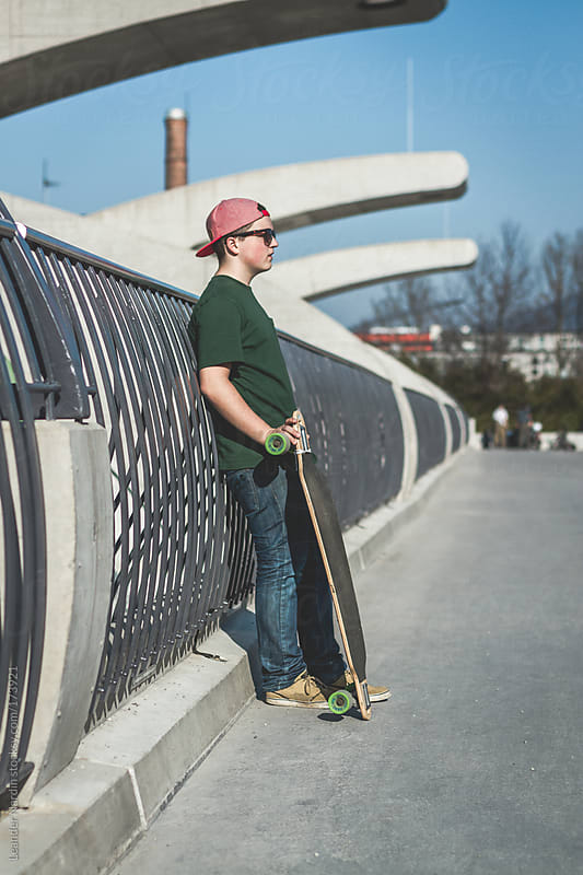 portrait of a teenager with his longboard by Leander Nardin for Stocksy United