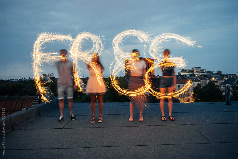 Young people on a rooftop painting the word 'free' with sparklers. by VegterFoto for Stocksy United