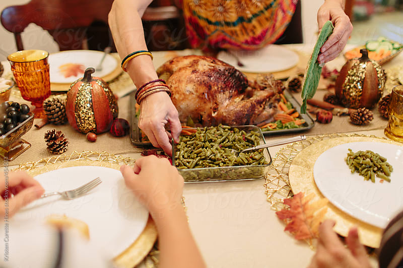 A mother putting green beans down on the dinner table during Thanksgiving.  by Kristen Curette Hines for Stocksy United