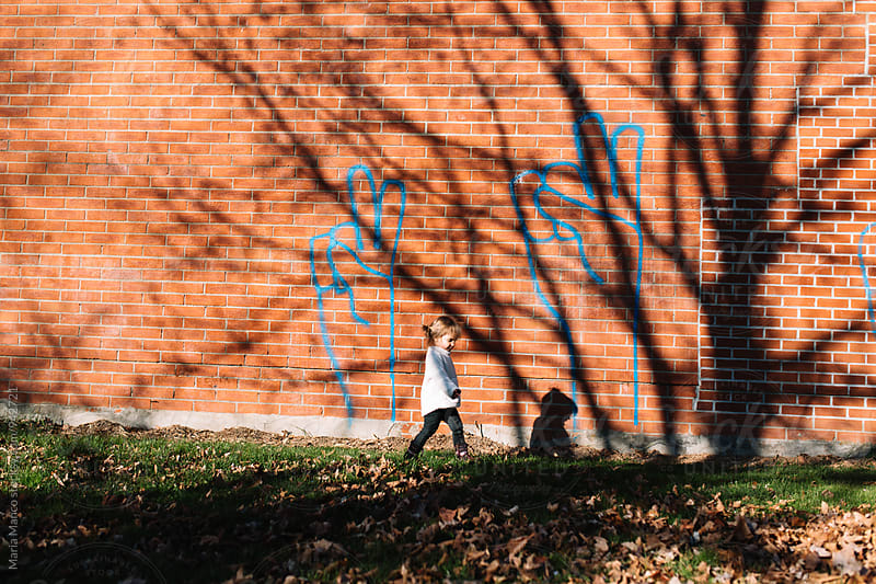 child in front of peace sign graffiti by Maria Manco for Stocksy United