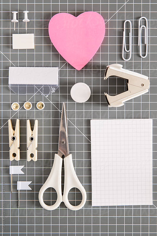 White office tools and pink notepad on grey background by Melanie Kintz for Stocksy United