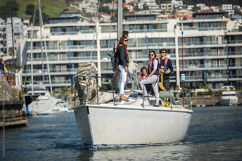 Young active group of friends sailing yacht on ocean harbor by Jonathan Caramanus for Stocksy United