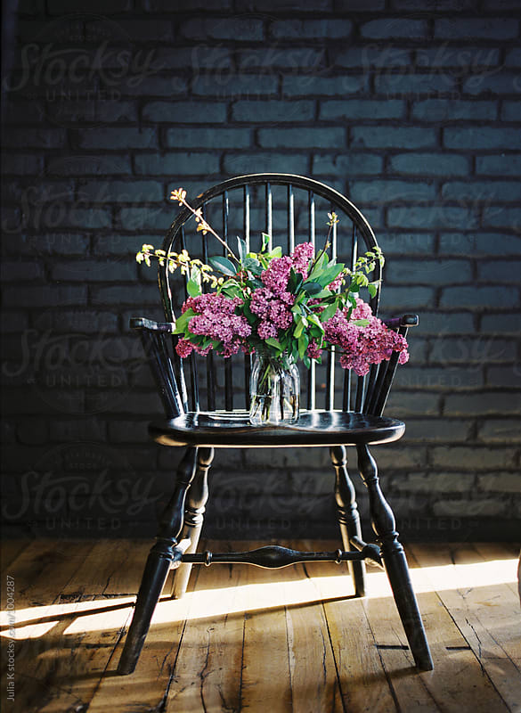 Lilac flowers bouquet on a chair by Julia Kaptelova for Stocksy United