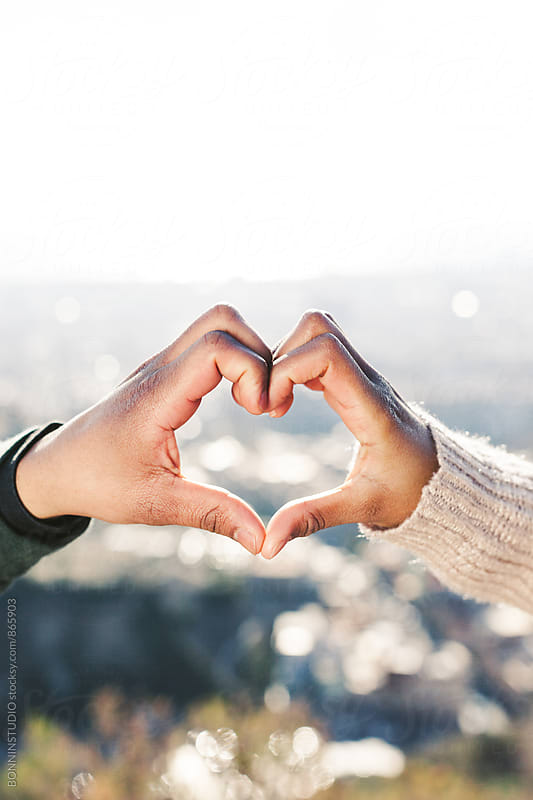 Couple with heart-shaped hands above city. by BONNINSTUDIO for Stocksy United