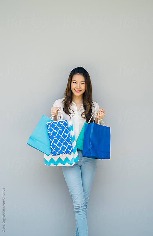 Beautiful woman holding shopping bags by Alita Ong for Stocksy United