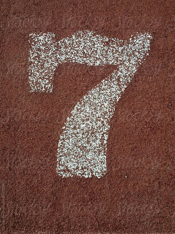 white number seven painted on an running track by German Parga for Stocksy United