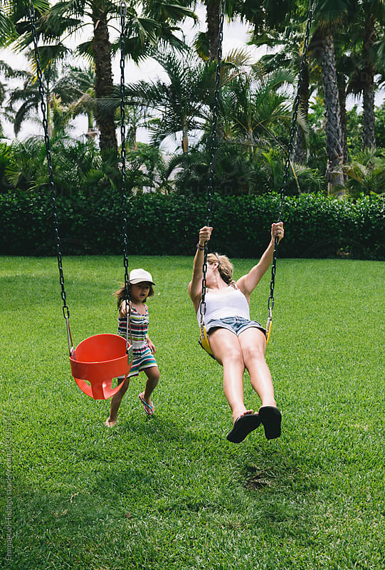 Mother and daughter playing on the swing in a tropical resort by Emmanuel Hidalgo for Stocksy United