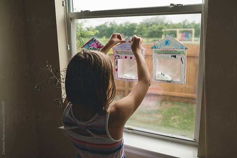 Girl hanging homeschool project  by Courtney Rust for Stocksy United