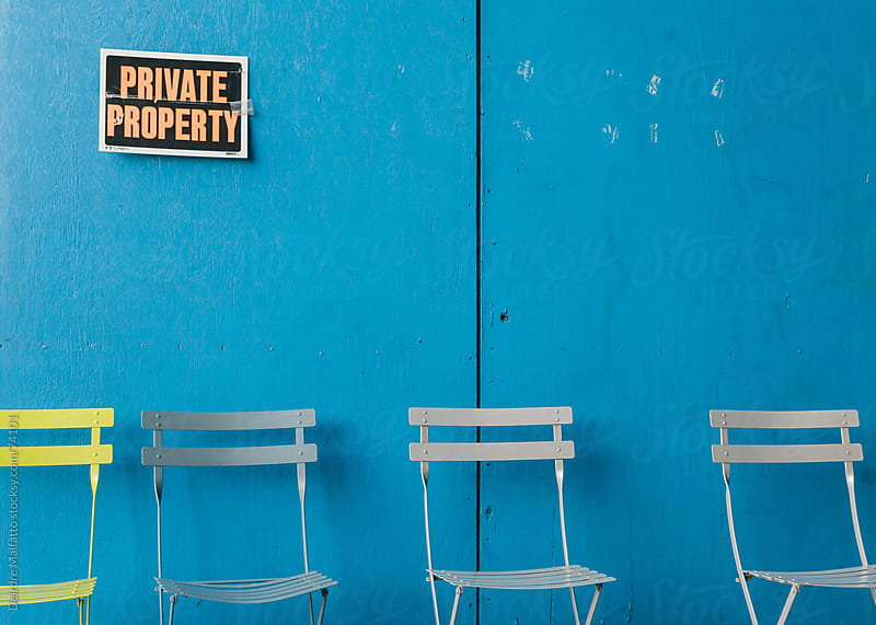 Empty chairs and a blue wall with a private property sign by Deirdre Malfatto for Stocksy United