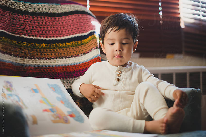 Little kid reading picture book by Lauren Naefe for Stocksy United