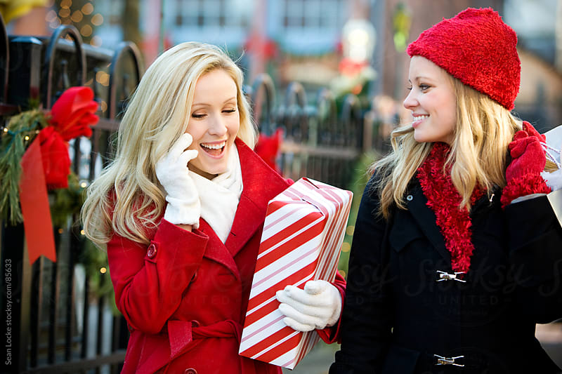 Christmas: Woman Gets a Call While Out with Friend by Sean Locke for Stocksy United