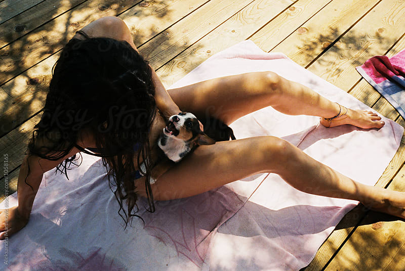 A girl playing with a puppy by Aleksandra Martinovic for Stocksy United