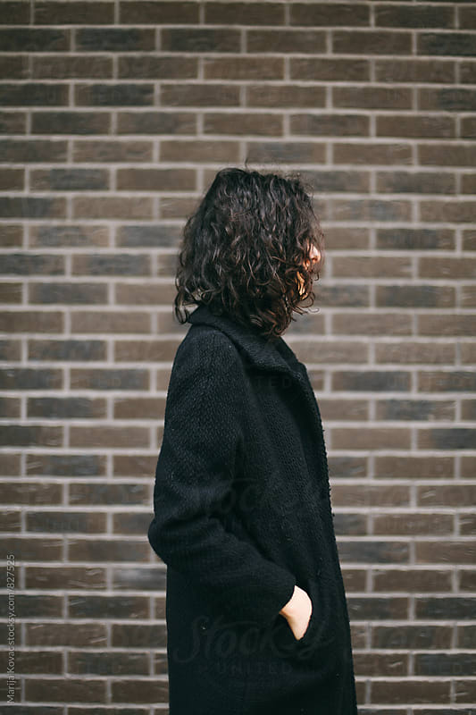Curly woman in a black coat, vertical by Marija Kovac for Stocksy United