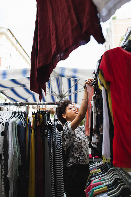 Young woman shopping for clothes at marketplace by michela ravasio for Stocksy United