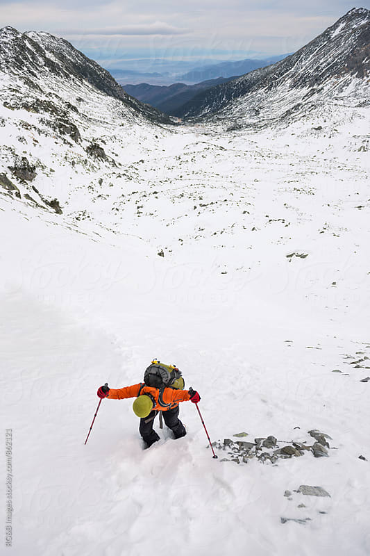 Mountaineer hiking up a snow covered slope by RG&B Images for Stocksy United