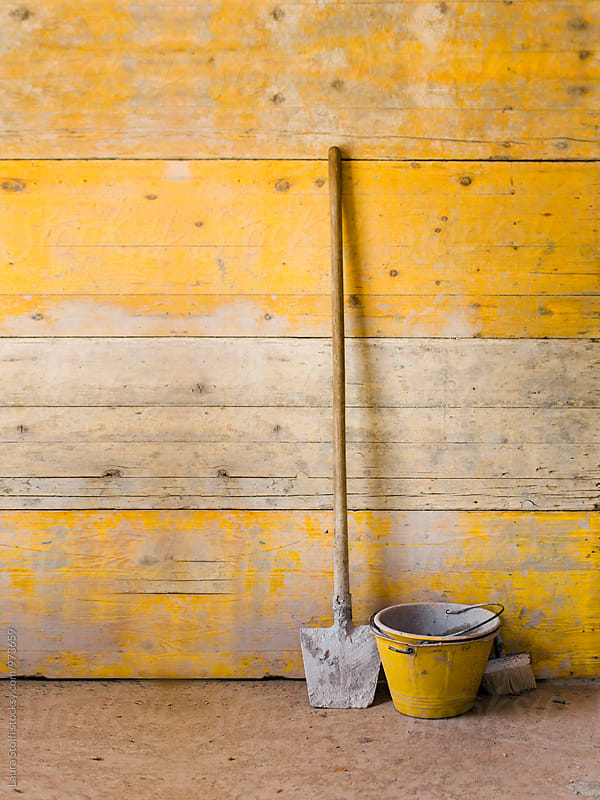 Working carpenter's tools in front of temporary wooden yellow wall by Laura Stolfi for Stocksy United