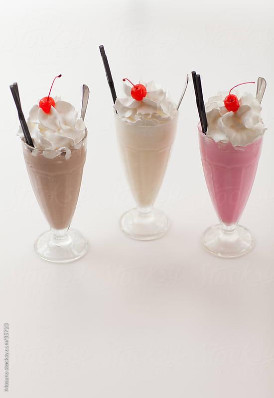 Three milk shakes on a white table. by Mosuno for Stocksy United