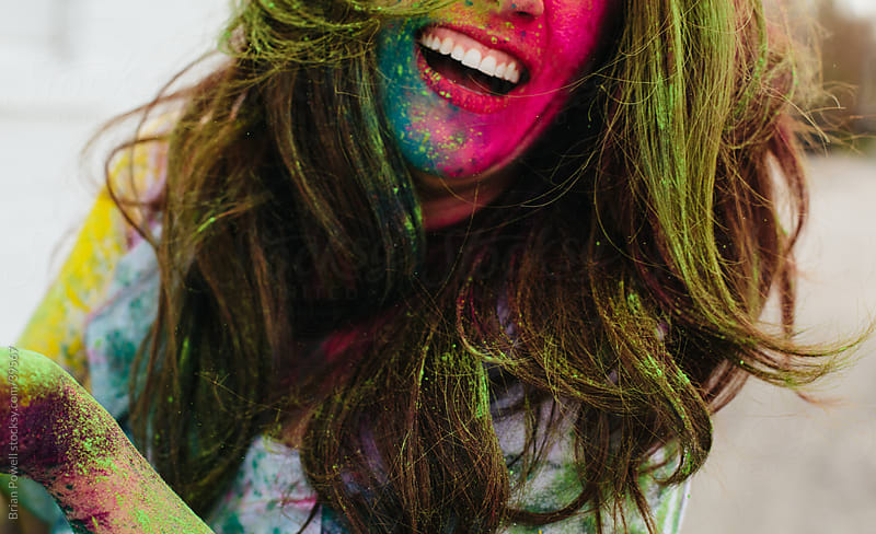 joyful woman with holi paint by Brian Powell for Stocksy United