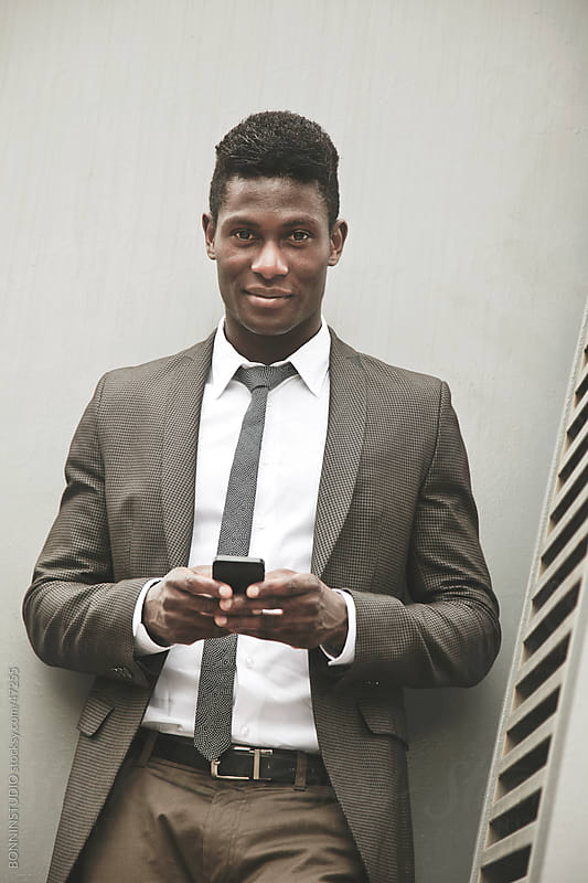 African young businessman looking at camera with a smartphone by BONNINSTUDIO for Stocksy United