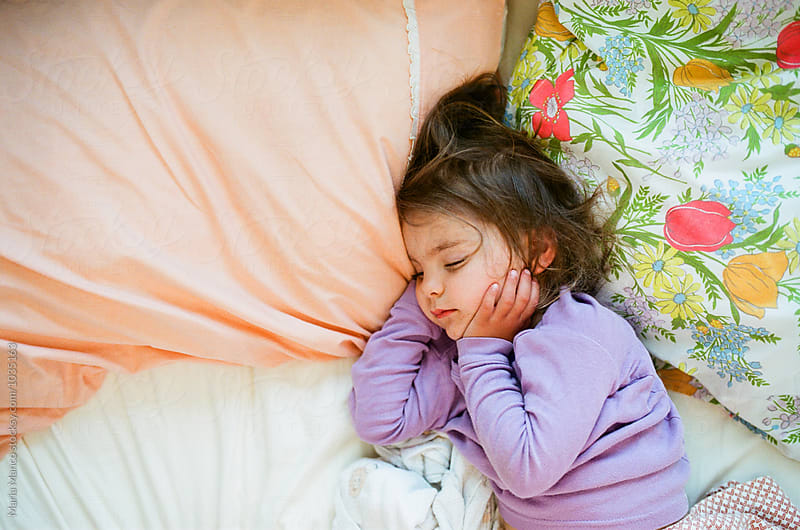 Little girl sleeping in bed by Maria Manco for Stocksy United