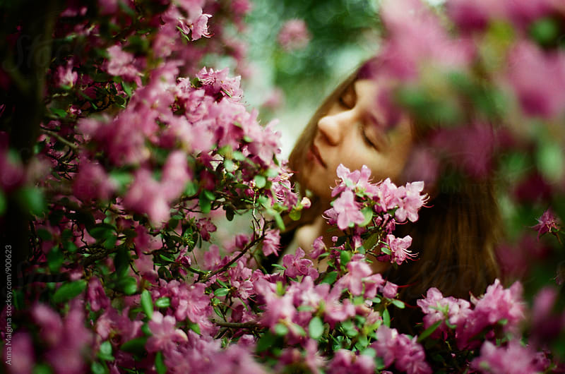 A film portrait of young beautiful woman standing between rose flowers by Anna Malgina for Stocksy United