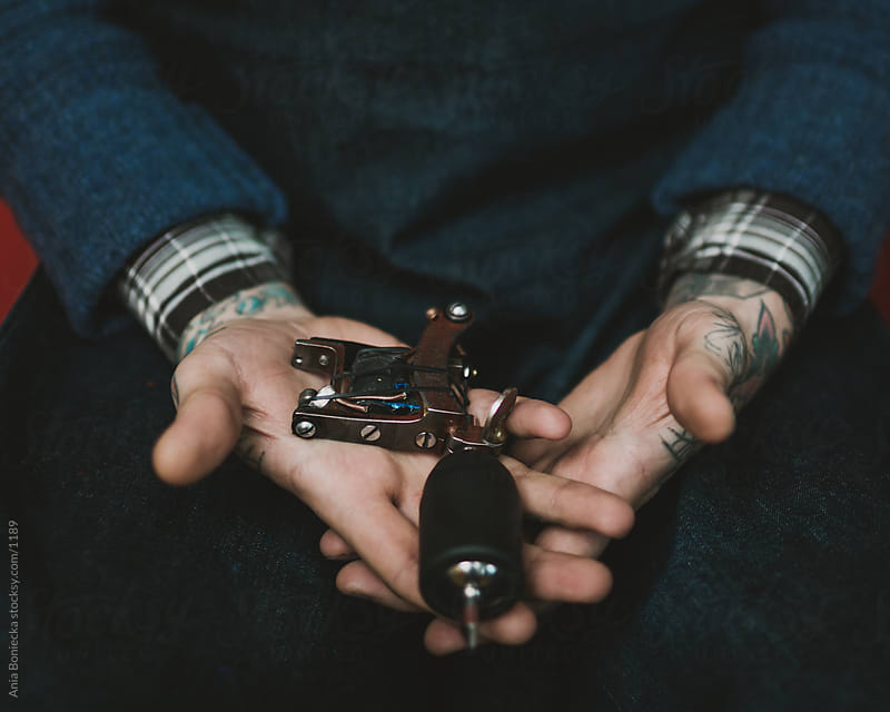 Tattoo artist holding his tool by Ania Boniecka for Stocksy United