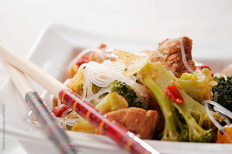 Asian food with cellophane or glass noodles and chopsticks by Ferenc Boros for Stocksy United
