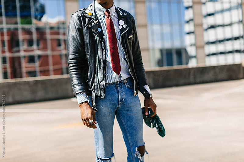 A man wearing a leather jacket & ripped blue jeans by Kristen Curette Hines for Stocksy United