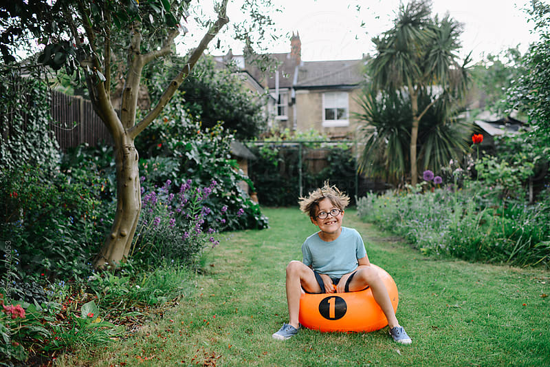 Boy pulling silly face on space hopper by Kirstin Mckee for Stocksy United